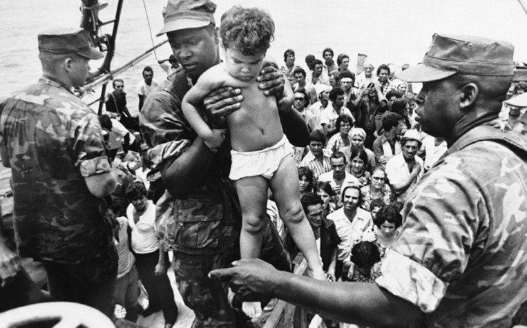 A U.S. Marine carries a child off a boat in Key West. May 1980. (FERNANDO YOVERA/AP)